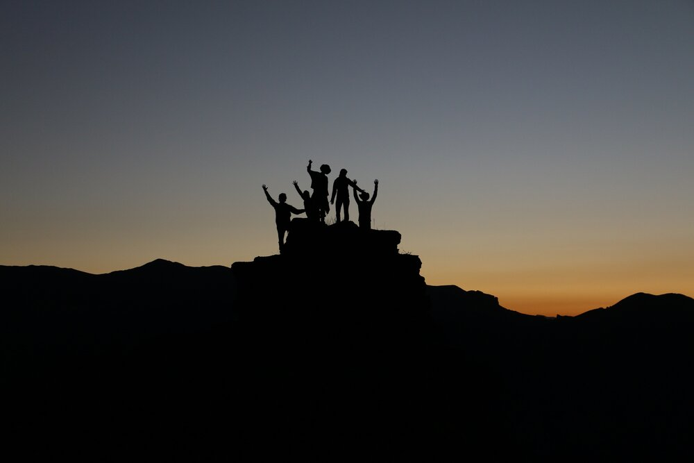 Silhouette of people standing on mountain during a sunrise.