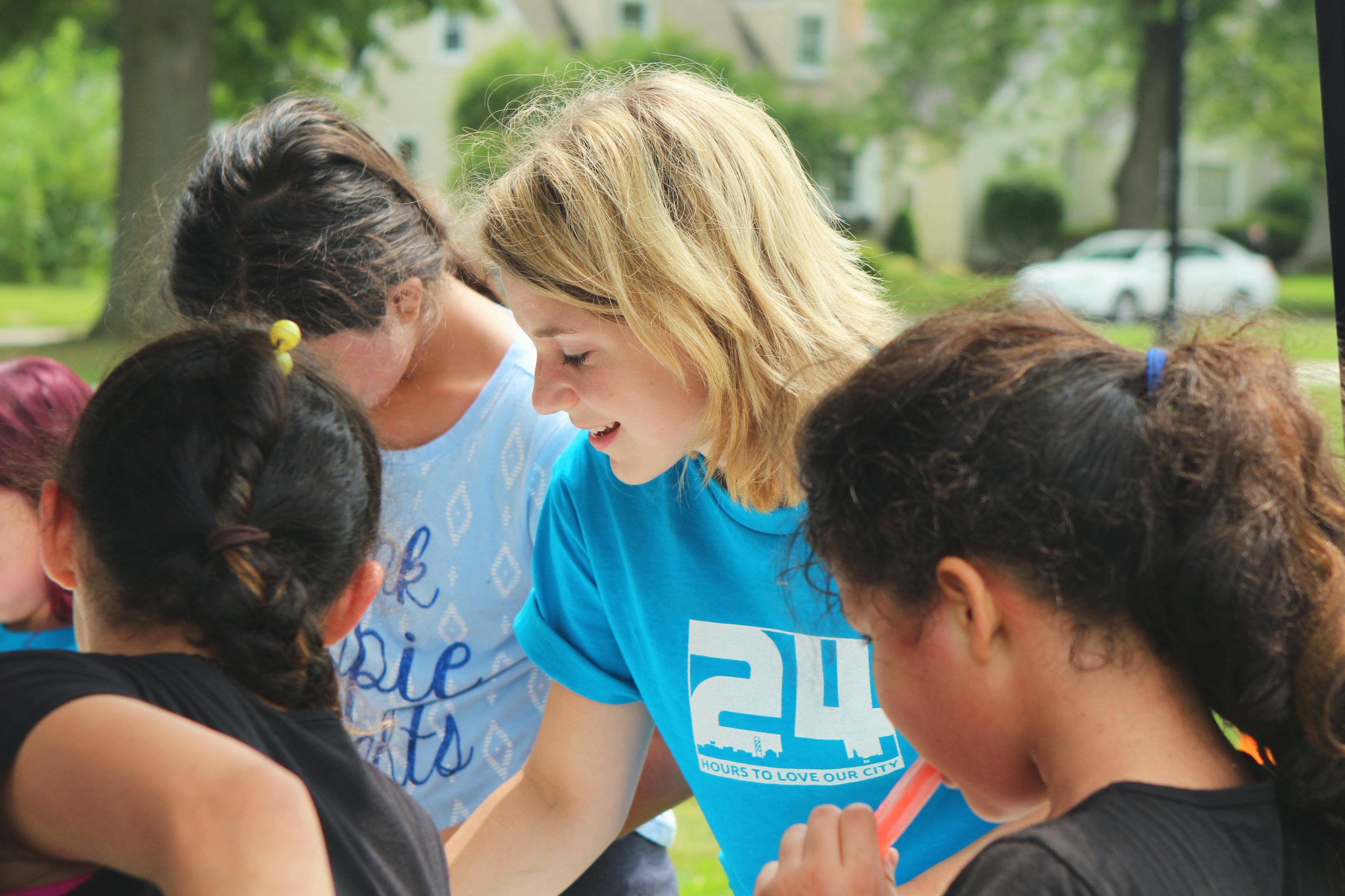 Blonde woman in blue shirt volunteering around children