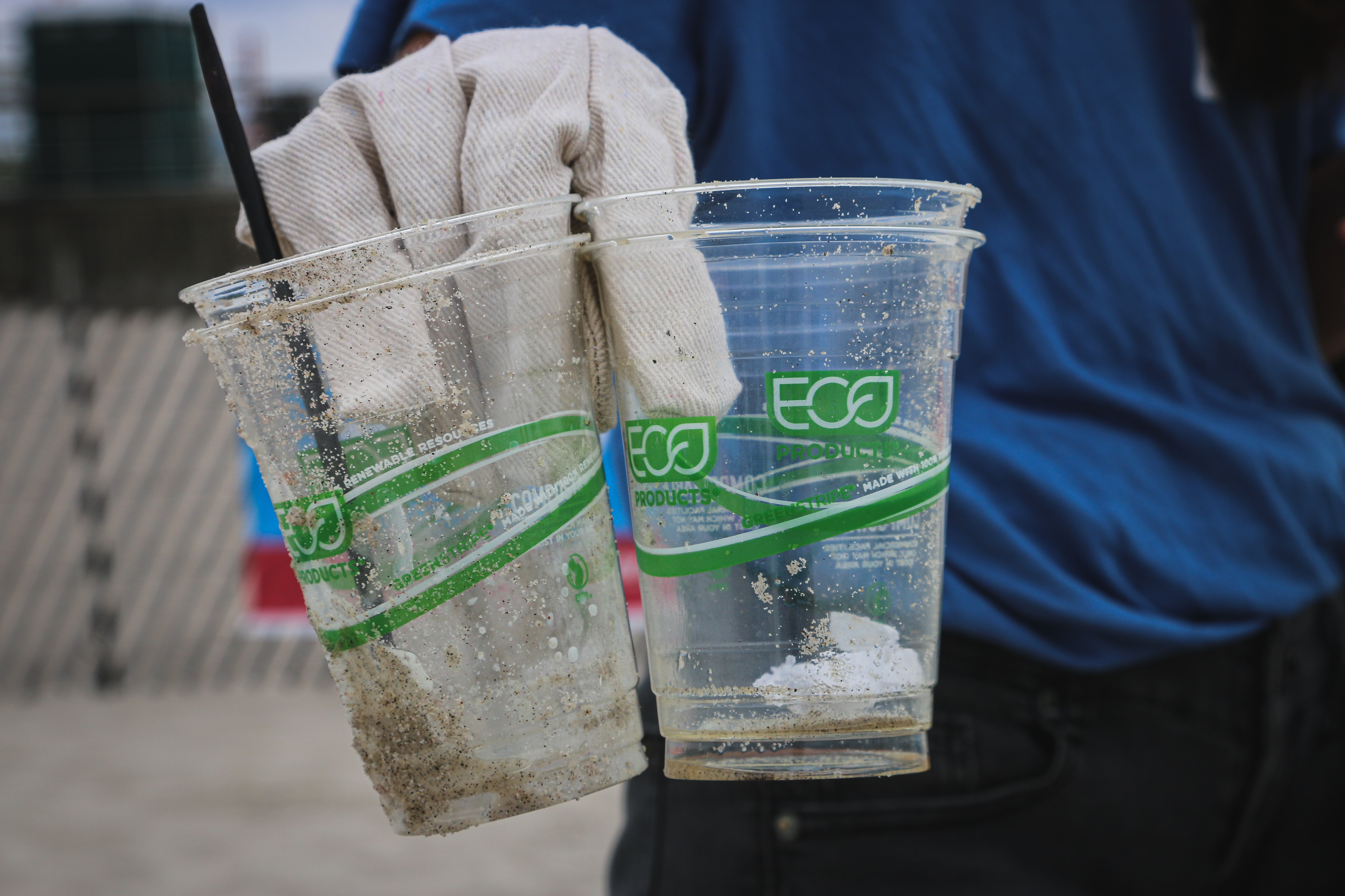 Two clear plastic cups about to be recycled being held